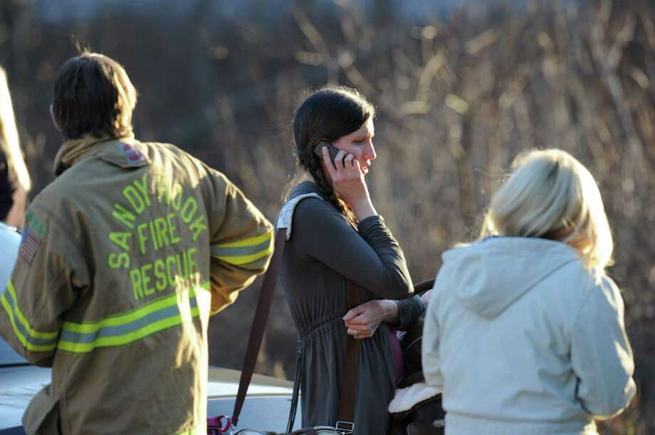 An unidentified woman makes a phone call on December 14, 2012 at the aftermath of  a school shooting at a Connecticut elementary school  that brought police swarming into the leafy neighborhood, while other area schools were put under lock-down, police and local media said. Local media quoted  that the gunman had died at the Sandy Hook Elementary School in Newtown, Connecticut, northeast of New York City.  At least 27 people, including 18 children, were killed on Friday when at least one shooter opened fire at an elementary school in Newtown, Connecticut, CBS News reported, citing unnamed officials. AFP PHOTO/DON EMMERT        (Photo credit should read DON EMMERT/AFP/Getty Images) Photo: Associated Press