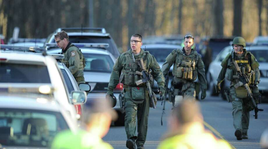State Police inspect the area on December 14, 2012 at the aftermath of  a school shooting at a Connecticut elementary school  that brought police swarming into the leafy neighborhood, while other area schools were put under lock-down, police and local media said. Local media quoted  that the gunman had died at the Sandy Hook Elementary School in Newtown, Connecticut, northeast of New York City.  At least 27 people, including 18 children, were killed on Friday when at least one shooter opened fire at an elementary school in Newtown, Connecticut, CBS News reported, citing unnamed officials. AFP PHOTO/DON EMMERT        (Photo credit should read DON EMMERT/AFP/Getty Images) Photo: DON EMMERT, Associated Press / 2012 AFP