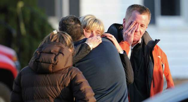 Unidentified people react on December 14, 2012 at the aftermath of  a school shooting at a Connecticut elementary school  that brought police swarming into the leafy neighborhood, while other area schools were put under lock-down, police and local media said. Local media quoted  that the gunman had died at the Sandy Hook Elementary School in Newtown, Connecticut, nort