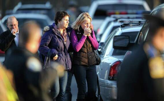 Unidentified people on December 14, 2012 leave the scene at the aftermath of  a school shooting at a Connecticut elementary school  that brought police swarming into the leafy neighborhood, while other area schools were put under lock-down, police and local media said. Local media quoted  that the gunman had died at the Sandy Hook Elementary School in Newtown, Connecticut, northeast of New York City.  At least 27 people, including 18 children, were killed on Friday when at least one shooter opened fire at an elementary school in Newtown, Connecticut, CBS News reported, citing unnamed officials. AFP PHOTO/DON EMMERT        (Photo credit should read DON EMMERT/AFP/Getty Images) Photo: DON EMMERT, Associated Press / 2012 AFP