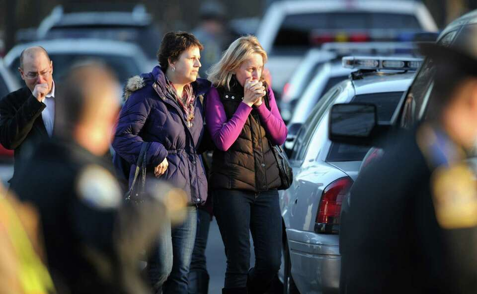 Unidentified people on December 14, 2012 leave the scene at the aftermath of  a school shooting at a
