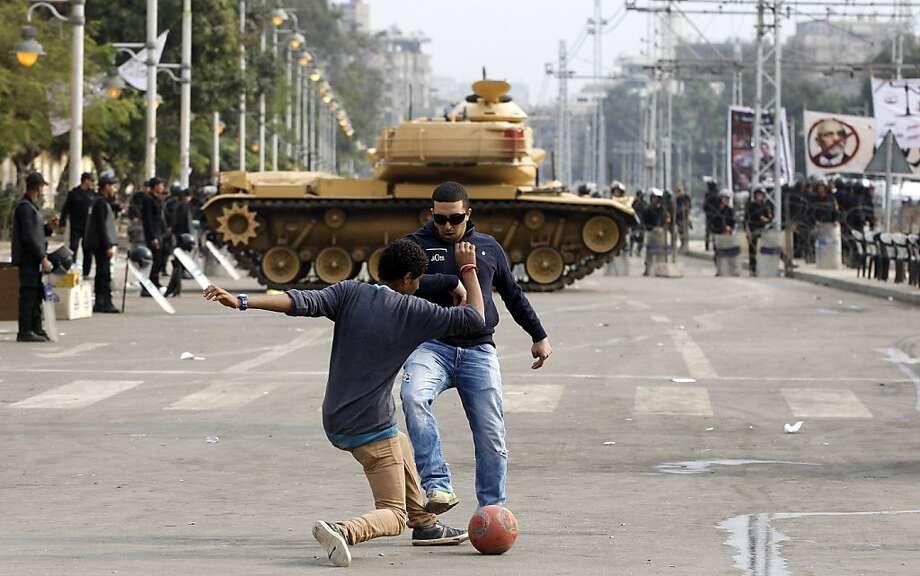 Ignoring the tank maneuvering behind them, protesters play soccer near the presidential palace in Cairo. Egypt was to begin voting Saturday on a contentious draft constitution that has plunged the country into turmoil and deeply divided the nation. Photo: Petr David Josek, Associated Press