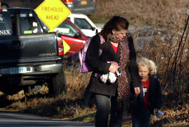 Families leave the Sandy Hook Firehouse where they gathered following a shooting at nearby Sandy Hook Elementary School in Newtown, Conn., on Friday, Dec. 14, 2012. Photo: Christian Abraham / Connecticut Post