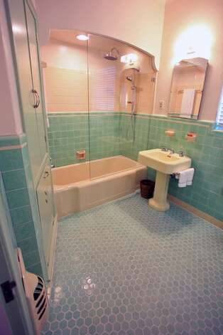The bathroom is original except the upper half of the tile and the glass wall. (Danny Warner)
