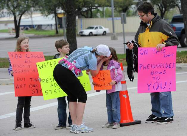 Erin Belanger stops to kiss her children as she makes the turn onto Main Street in downtown Beaumont during the Gusher Marathon, Saturday March 10, 2012.  Her husband Joey, right, holds her coat.  Dave Ryan/The Enterprise