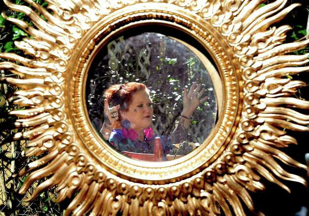 "Patricia ""Patches"" Droddy, while sitting in her front yard enjoying the peace and quiet of her ""Mystic Woods of Whispering Spirits"" that she has created, is reflected in one of the many mirrors that hang from the tree and bush branches.  Her home and the gardens around it are an ongoing art project, even after 20 years.  Dave Ryan/The Enterprise"
