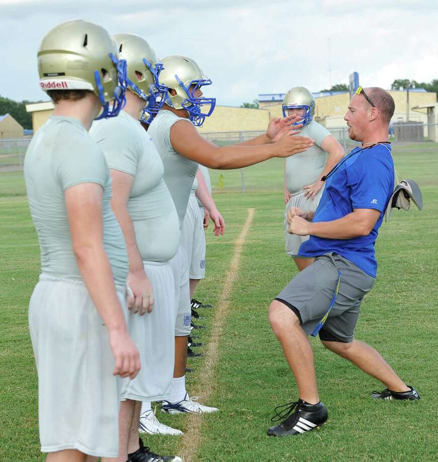Coach Marcus Zarosky, right, gives instructions to his players as he demonstrates the stance he wants them to hold as they go through a drill. Hamshire-Fannett held one of their football practices Wednesday night, August 8, 2012 and started at 6 p.m. Dave Ryan/The Enterprise