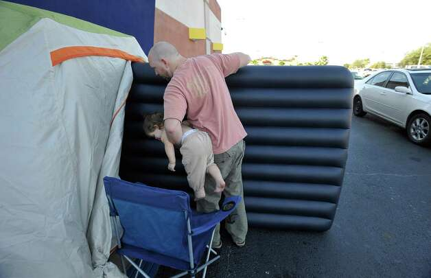 Seasoned Black Friday shoppers like Jared Gilthorpe, seen here carrying both his daughter Charlie, and an air mattress into his tent,   and friend Marcus Paterno, are already lined up outside of Best Buy, hoping to scoop up deals on electronics. They are the first in line at the Best Buy in Beaumont.    Dave Ryan/The Enterprise