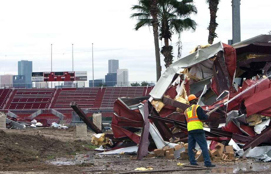 A crewman sprays water on a portion of Robertson Stadium during its demolition on December 10. (Cody Duty / Chronicle)