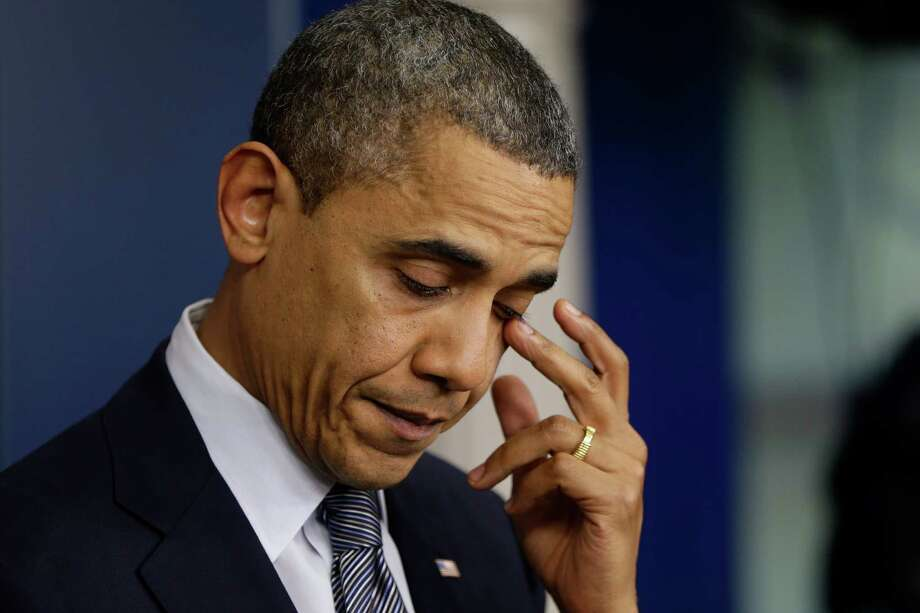 President Barack Obama wipes his eye as he speaks about the elementary school shooting in Newtown, Conn., Friday, Dec. 14, 2012, in the briefing room of the White House in Washington. (AP Photo/Charles Dharapak) Photo: Charles Dharapak, STF / AP