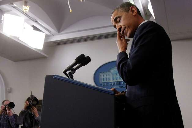 President Barack Obama wipes his eye as he speaks about the school shooting in Newtown, Conn., Friday, Dec. 14, 2012, in the briefing room of the White House in Washington. (AP Photo/Charles Dharapak) Photo: Charles Dharapak, STF / AP