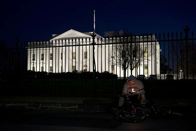 Brian Farnkoff, 30, of Boston, sits by the White House fence holding a candle, as supporters of gun control gather on Pennsylvania Avenue in front of the White House, in Washington, Friday, Dec. 14, 2012, during a vigil for the victims of the shooting at Sandy Hook Elementary School in Newtown, Ct., and to call on President Obama to pass strong gun control laws. (AP Photo/Jacquelyn Martin) Photo: Jacquelyn Martin, Associated Press