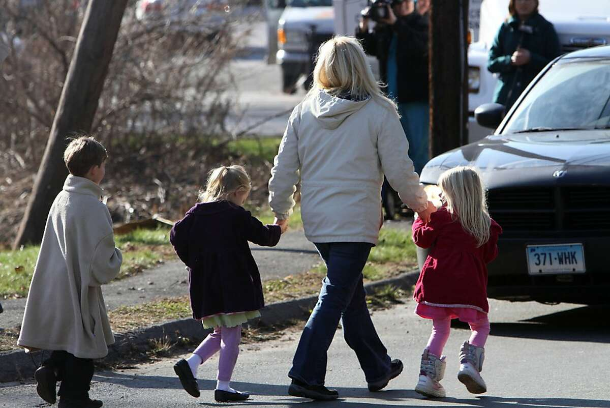 A parents leads children away from the Sandy Hook Elementary School in Newtown, Conn., following the shootings.