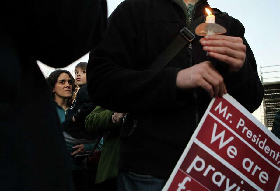 WASHINGTON, DC - DECEMBER 14:  Local resident Rachel Perrone (L) and her five-year-old son Joe (2nd L) join other people outside the White House to participate in a candle light vigil to remember the victims at the Sandy Hook Elementary School shooting in Newtown, Connecticut December 14, 2012 in Washington, DC.  According to reports, there are about 27 dead, 20 of them children, after a gunman opened fire in at the Sandy Hook Elementary School. The shooter was also killed. Photo: Alex Wong, Getty Images / 2012 Getty Images