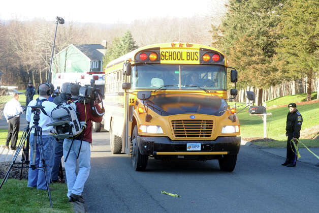 A school bus carrying high school students drives upYogananda Street in Newtown, Conn., where the mother of shooting suspect Adam Lanza was found shot to death on Friday, Dec. 14, 2012. Photo: Ned Gerard / Connecticut Post