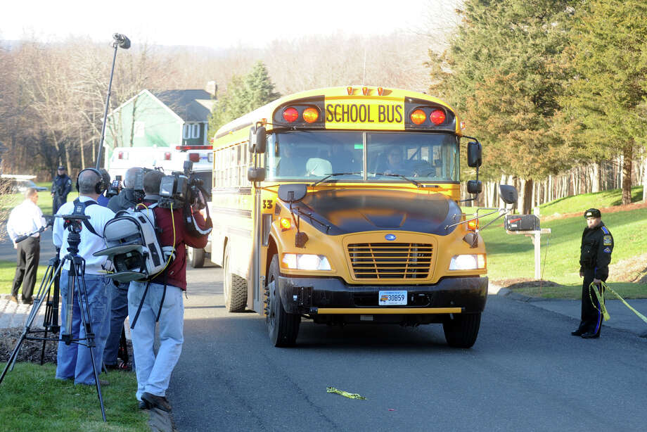 A school bus carrying high school students drives up Yogananda Street in Newtown, Conn., where the mother of shooting suspect Adam Lanza was found shot to death on Friday, Dec. 14, 2012. Photo: Ned Gerard / Connecticut Post