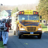 A school bus carrying high school student drives up Yogananda Street, in Newtown, Conn., where one adult was found dead in a home following the mass shooting at Sandy Hook Elementary School Dec. 14th, 2012.