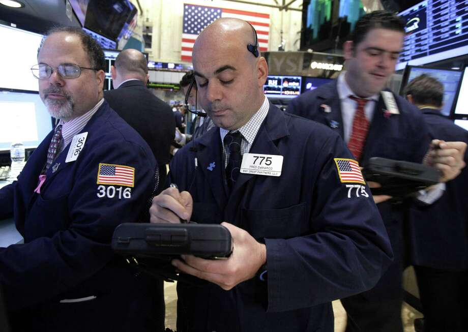 FILE- In this Thursday, Dec. 6, 2012, file photo, Trader Fred DeMarco, center works on the floor of the New York Stock Exchange. World stock markets swung higher Friday Dec. 14, 2012 after a survey showed an improvement in China's manufacturing, offsetting gloom from a sharp drop in Japanese business confidence. (AP Photo/Richard Drew, File) Photo: Richard Drew