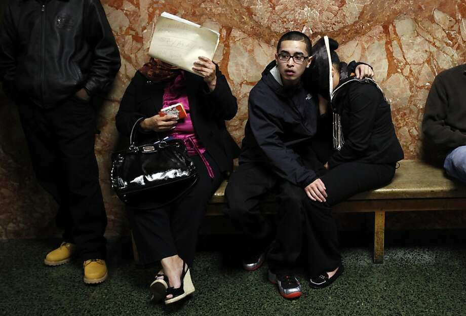 Tyler Miller (right, with face hidden) of Hercules, the fifth defendant in a San Francisco killing, awaits her arraignment. Photo: Sarah Rice, Special To The Chronicle