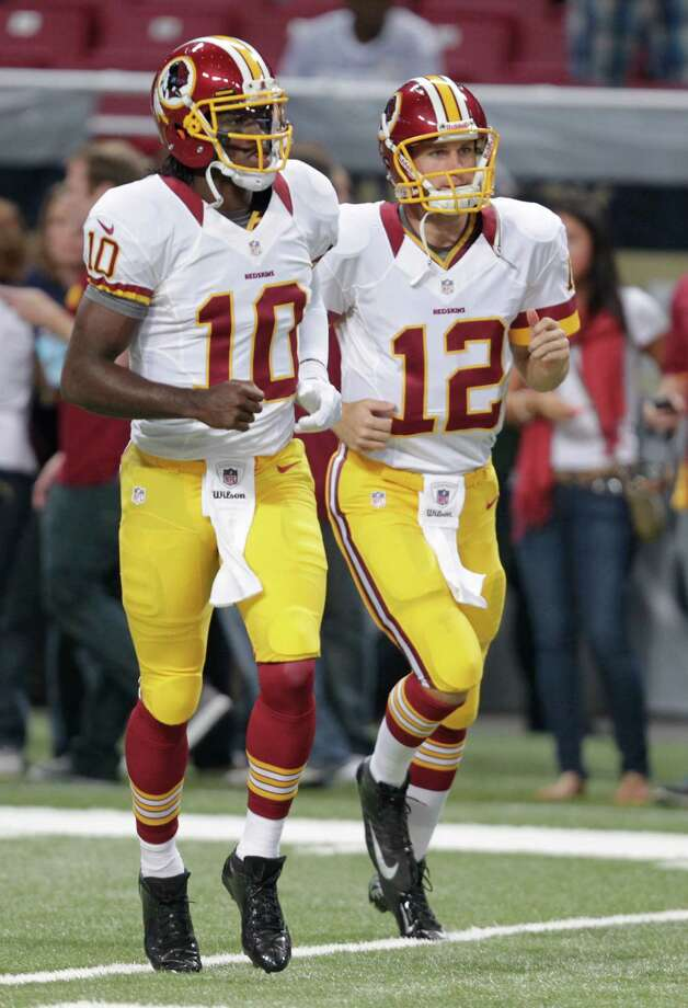 FILE - In this Sept. 16, 2012, file phot, Washington Redskins quarterbacks Robert Griffin III (10) and Kirk Cousins (12) warm up before the start of an NFL football game against the St. Louis Rams in St. Louis. A rookie will start at quarterback for the Redskins on Sunday. It will be either Griffin or Cousins facing the Cleveland Browns.  (AP Photo/Tom Gannam, File) Photo: Tom Gannam, Associated Press / FR45452 AP