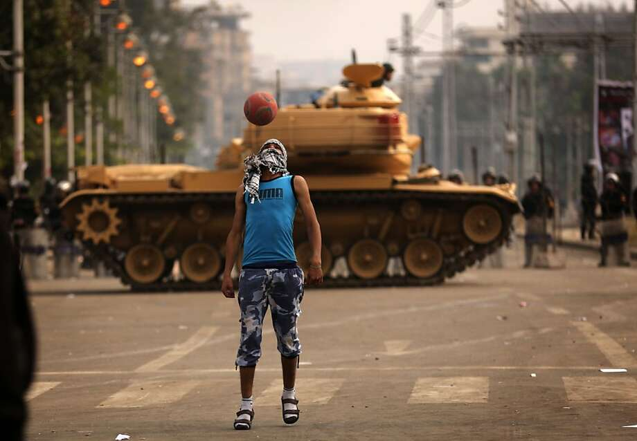A supporter of the opposition to Egyptian President Mohamed Morsi plays football next to a Republican Guard tank deployed outside the presidential palace in Cairo on December 14, 2012. Egypt's 51 million voters are being called to vote over the next two weekends in a referendum on a draft constitution backed by Islamists, including Morsi, but denounced by the secular opposition. Photo: Patrick Baz, AFP/Getty Images