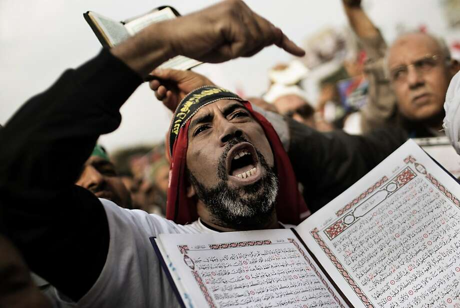 TOPSHOTS A supporter of Egypt's President Mohamed Morsi and the Muslim Brotherhood holds a copy of the Koran, Islam's holy book, as he shouts slogans during a demonstration in Cairo's Nasr City on December 14, 2012. A draft constitution supported by Morsi and bitterly contested by the secular-leaning opposition is dividing Egypt on the eve of a referendum on the proposed charter. AFP PHOTO/MARCO LONGARIMARCO LONGARI/AFP/Getty Images Photo: Marco Longari, AFP/Getty Images