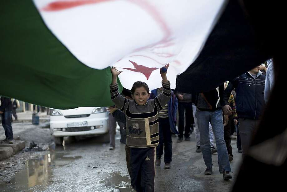 A Syrian child marches under a revolutionary flag during a weekly demonstration in Aleppo, Syria, Friday, Dec. 14, 2012. Photo: Manu Brabo, Associated Press