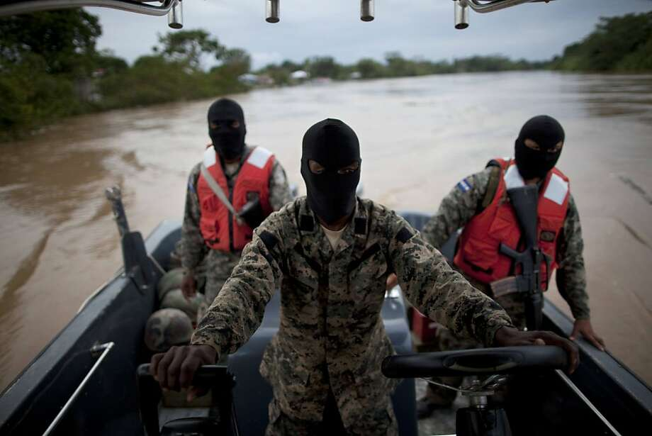 Honduran navy officers look for drug activity in May. Drug gangs hold control of much of the country, which is struggling. Photo: Rodrigo Abd, Associated Press
