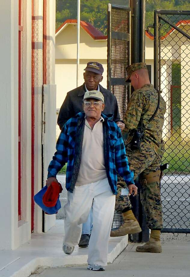 Harry Henry, 82, (rear) and Luis La Rosa, 79, leave after their shift at the U.S. base in Guantanamo, where they've worked for decades. Photo: Suzette Laboy, Associated Press