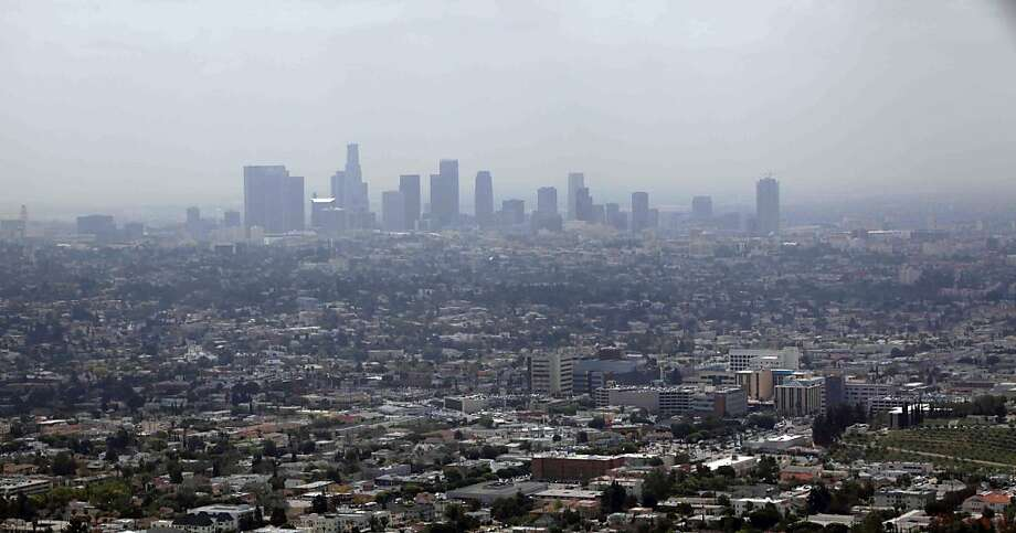 FILE - This April 28, 2009 file photo shows smog covering downtown Los Angeles. In its first major regulation since the election, the Obama administration will impose a new air quality standard that reduces by 20 percent the maximum amount of soot released into the air from smokestacks, diesel trucks and other sources of pollution. The Environmental Protection Agency (EPA) is set to announce the new standard on Friday, meeting a court deadline in a lawsuit by 11 states and public health groups.  (AP Photo/Nick Ut, File) Photo: Nick Ut, Associated Press