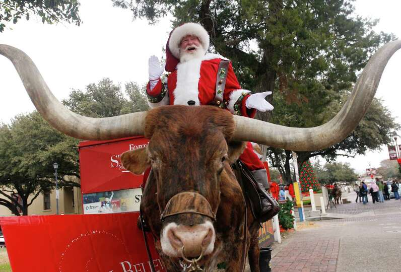 Texas longhorn, Sir Niles, gets to visit with Macy's Santa at the Fort Worth Stockyards Friday, Dec.