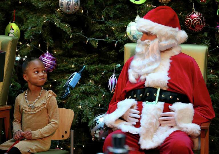 Five-year-old Jordyn Akyoko looks at a Santa Claus impersonator during a Christmas story reading by