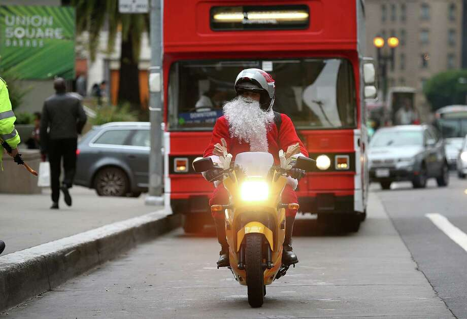 A man dressed as Santa Claus rides a motorcycle in Union Square on December 14, 2012 in San Francisco, California.  With less than two weeks before Christmas, San Franciscans are getting into the holiday spirit. Photo: Justin Sullivan, Getty Images / 2012 Getty Images