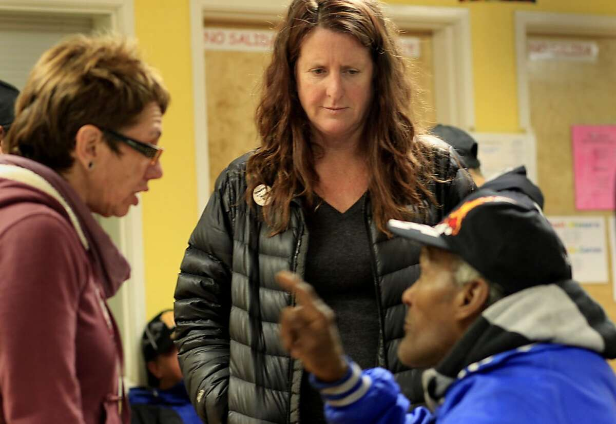 Jennifer Friedenbach (center) and Resource Center director Laura Guzman (left) listened to a homeless man at the center. The San Francisco Homeless Coalition will celebrate its 25 year anniversary shortly. The current head of the Coalition Jennifer Friedenbach visited the Mission Neighborhood Resource Center, a Coalition organization, Tuesday December 11, 2012.