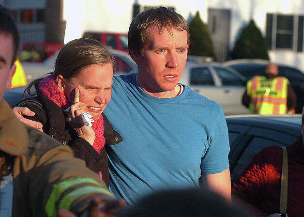 People leave the Sandy Hook Volunteer Fire House in tears after a shooting at the Sandy Hook Elementary School, Friday morning, Dec. 14, 2012 in Newtown, Conn. A man opened fire Friday inside two classrooms at the Connecticut elementary school where his mother was a teacher, killing 26 people, including 20 children, as youngsters cowered in corners and closets and trembled helplessly to the sound of shots reverberating through the building. Photo: AP