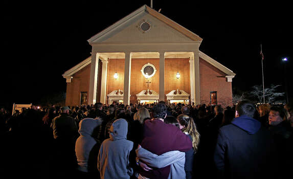 As hundreds stand outside St. Rose of Lima Roman Catholic Church, which was filled to capacity, a couple embrace during a healing service held in for victims of an elementary school shooting in Newtown, Conn., Friday, Dec. 14, 2012.  A gunman opened fire at Sandy Hook Elementary School in Newtown, killing 26 people, including 20 children. Photo: AP