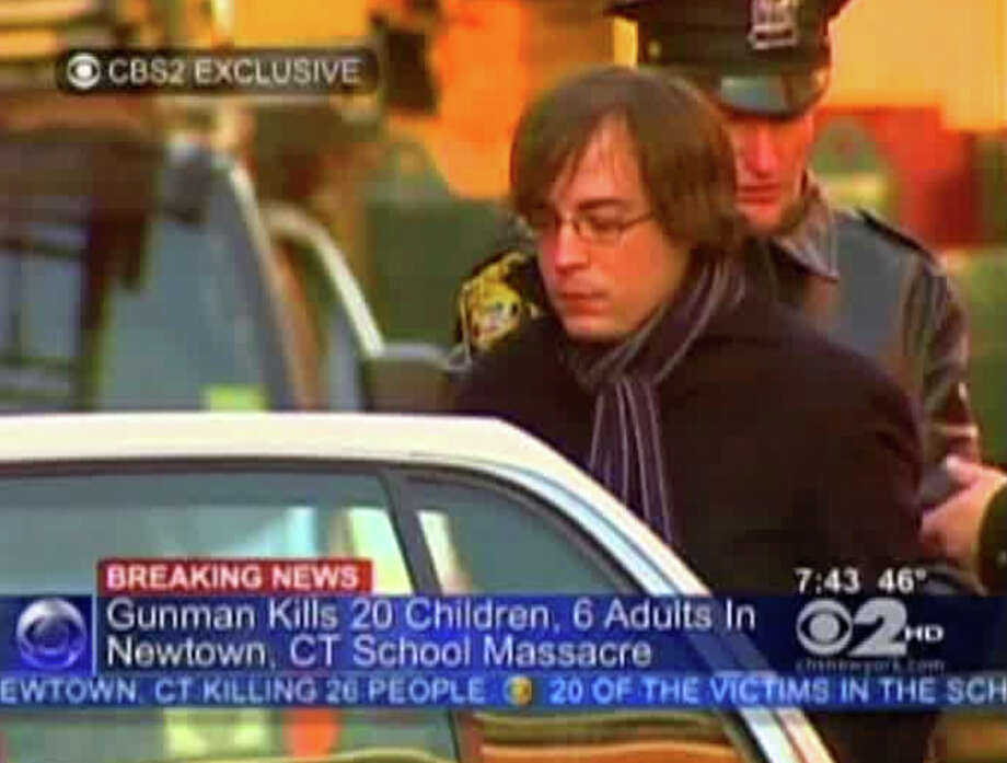 In this frame grab provided by WCBS in New York, Ryan Lanza, the 24-year-old brother of Sandy Hook Elementary School shooter Adam Lanza, is escorted by police into a cruiser in Hoboken, N.J., Friday, Dec. 14, 2012. Adam Lanza, 20, killed his mother at home and then opened fire Friday inside the elementary school where she taught, massacring 26 people, including 20 children, as youngsters cowered in fear to the sound of gunshots echoing through the building and screams coming over the intercom. (AP Photo/WCBS-TV) MANDATORY CREDIT: WCBS-TV Photo: Uncredited, TEL / WCBS-TV