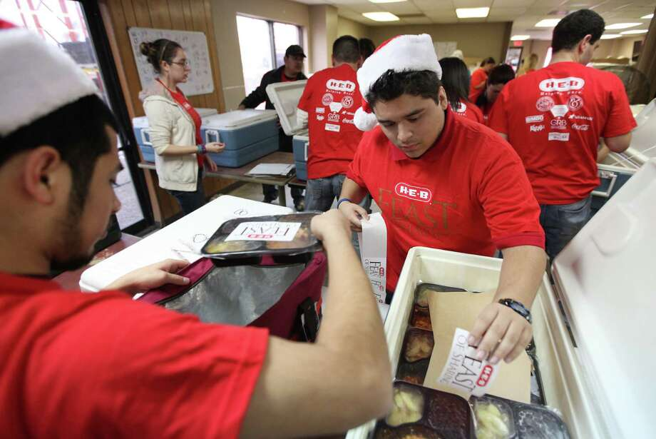 Jose Habes and Juan Cerda place labels on warm food in preparation to deliver holiday meals to homes as H-E-B hosted the 7th Annual Feast of Sharing. Photo: Mayra Beltran, Houston Chronicle / © 2012 Houston Chronicle