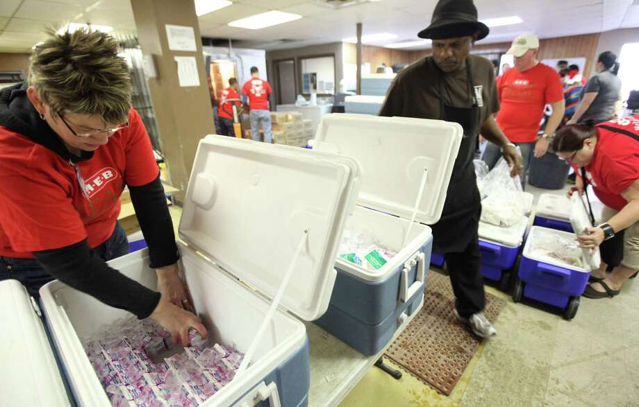 Shannon Simpson and Rev. Woodrow Barrett Senior assemble ice coolers with milk in preparation to deliver holiday meals to homes. Photo: Mayra Beltran, Houston Chronicle / © 2012 Houston Chronicle