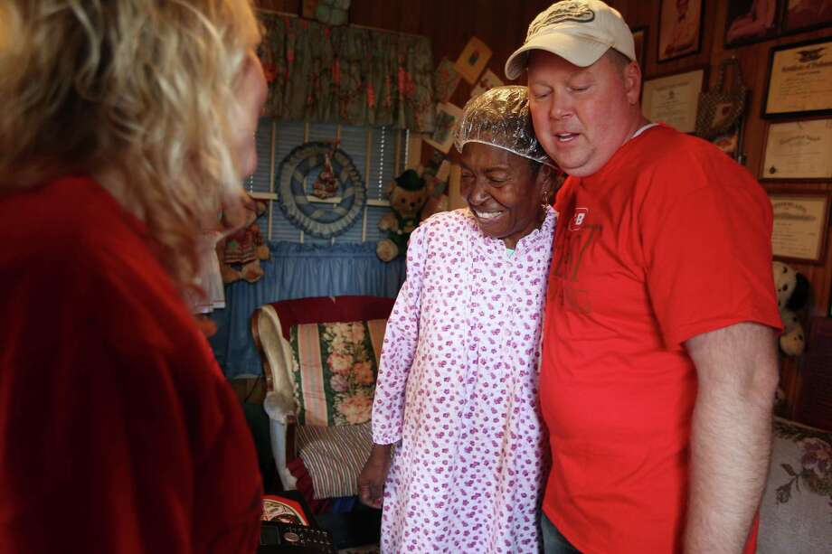 Heather Bennion looks at her husband Greg Bennion, HEB manager, as he gives a hug to Betty Wilson, 82, as they deliver holiday meals to homes. Photo: Mayra Beltran, Houston Chronicle / © 2012 Houston Chronicle