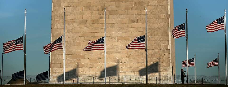 A National Park Service employee lowers flags at the Washington Monument to half-staff, which Presid