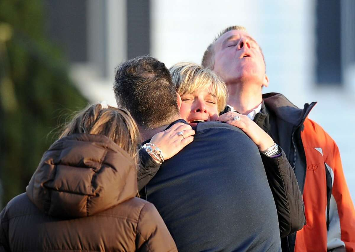 Unidentified people embrace on December 14, 2012 at the aftermath of a school shooting at a Connecticut elementary school that brought police swarming into the leafy neighborhood, while other area schools were put under lock-down, police and local media said. Local media quoted that the gunman had died at the Sandy Hook Elementary School in Newtown, Connecticut, northeast of New York City. At least 27 people, including 18 children, were killed on Friday when at least one shooter opened fire at an elementary school in Newtown, Connecticut, CBS News reported, citing unnamed officials. AFP PHOTO/DON EMMERTDON EMMERT/AFP/Getty Images