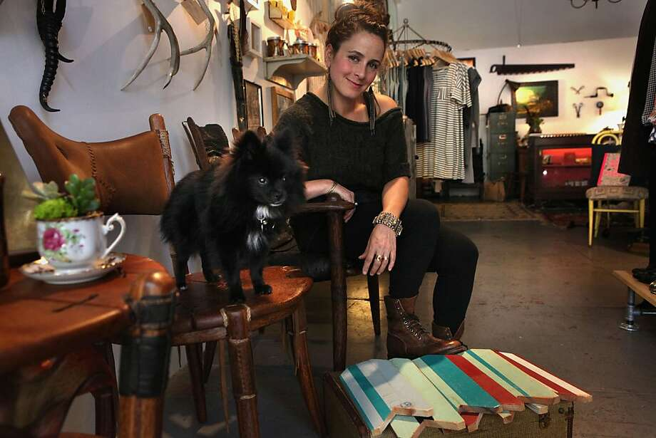Nicole Buffett and her Pomeranian sit on chairs made by Alameda artist Jamie Michaels in her Oakland store, Piper and John General Goods, which also showcases her artwork. Photo: Liz Hafalia, The Chronicle