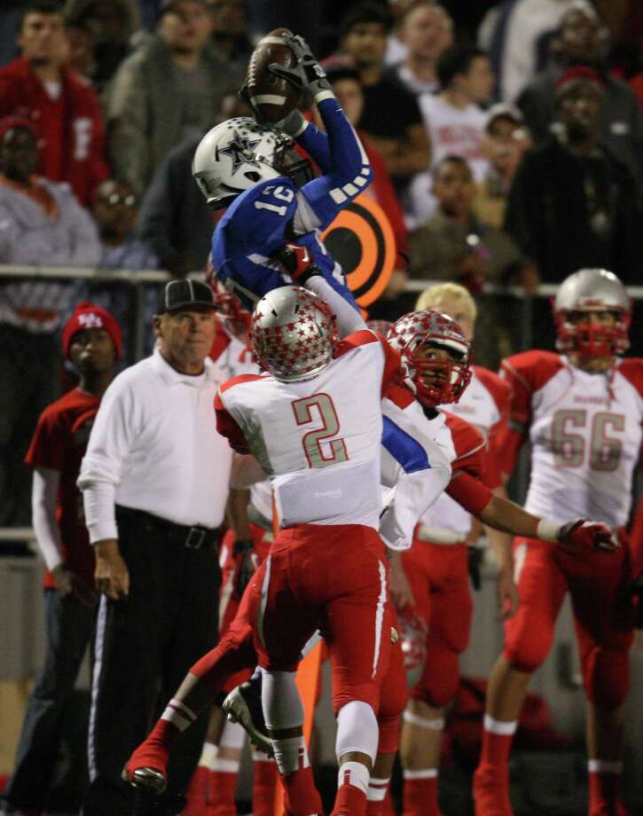 Navasota's Solomoin McGinty (12) makes a leaping reception over Bellville's Taylor Thompson (2) during the first half of a Class 3A state semifinal high school football game, Friday, December 14, 2012 at Waller ISD Stadium in Waller, TX. Photo: Eric Christian Smith, For The Chronicle