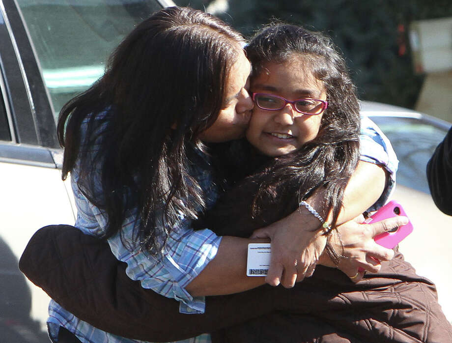 A woman and her daughter have a happy reunion at the Sandy Hook firehouse following Friday's mass shooting at the Sandy Hook Elementary School. Photo: Frank Becerra Jr., MBO / The Journal News
