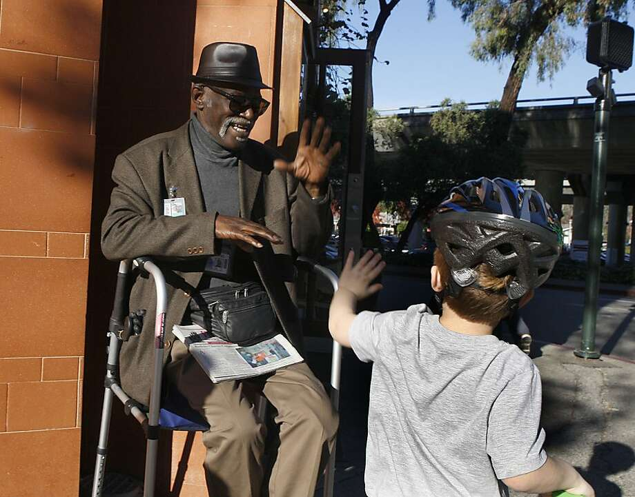 A passing friend greets Aldren Mayfield as he sells Street Spirit outside Oliveto restaurant on College Avenue in Rockridge. Photo: Liz Hafalia, The Chronicle