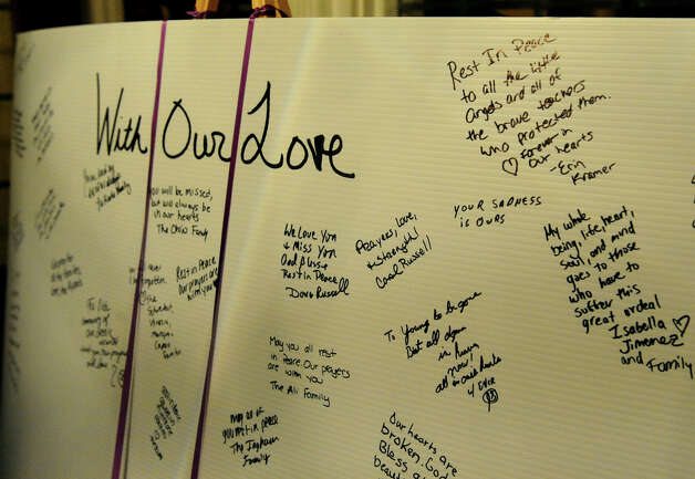 A signed poster sits in the foyer at St. Rose of Lima Church in Newtown, Conn., during a memorial service on Friday, Dec. 14, 2012. Photo: Christian Abraham / Connecticut Post