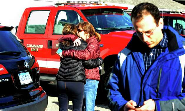 Parents of Sandy Hook Elementary School students console each other outside the Sandy Hook Firehouse after shootings at the school Friday, Dec. 14, 2012. Photo: Michael Duffy / The News-Times