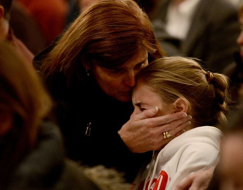 Mourners gather inside the St. Rose of Lima Roman Catholic Church at a vigil service for victims of the Sandy Hook Elementary School shooting that left at least 27 people dead, many of them young children, in Newtown, Connecticut, USA, 14 December 2012.  A heavily armed young gunman slaughtered 20 small children and six adults at a school in an idyllic Connecticut town on Friday, in one of the worst mass shootings in US history.  Connecticut State Police spokesman Lieutenant Paul Vance said 18 children were shot dead inside Sandy Hook Elementary School and that two more died of their wounds in hospital.  Six adults at the school were killed, Vance said, before the killer was shot -- either by his own hand or police. US media said the school principal was among those killed.  Hours after the massacre, there was still no clue to the motives for the shootings in Newtown, a wooded and picturesque small town north-east of New York City.   AFP PHOTO / POOL / ANDREW GOMBERTANDREW GOMBERT/AFP/Getty Images Photo: Andrew Gombert, AFP/Getty Images