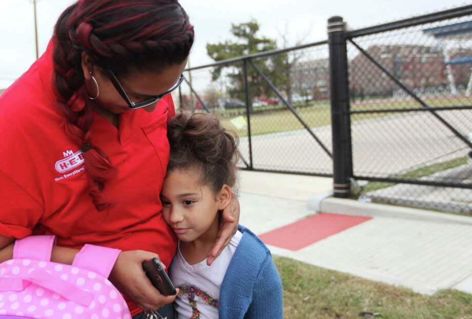 Janita Bautista hugs daughter Liliana Lara, 6, outside Crockett Elementary School in Houston after she reacts to hearing details about the elementary mass shooting in Connecticut that left 29 people dead on Friday. Photo: Mayra Beltran, Staff / © 2012 Houston Chronicle